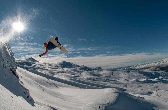 Guy on snowboard mid air on ski slopes with sun in background.