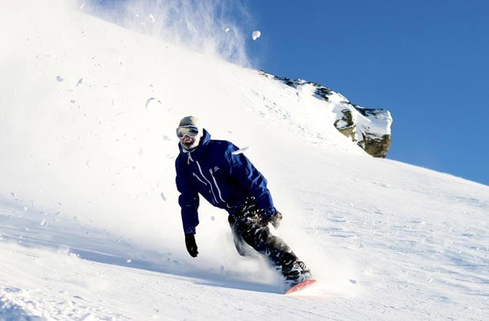 Guy snowboarding down slope fast and wearing blue jacket + beanie.