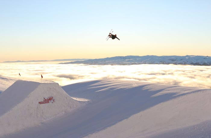 Guy mid air on skis after taking off on ski ramp. Clouds lying low and mountain in background.