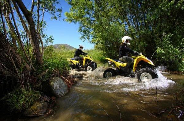 2 guys riding on yellow quad bikes through water