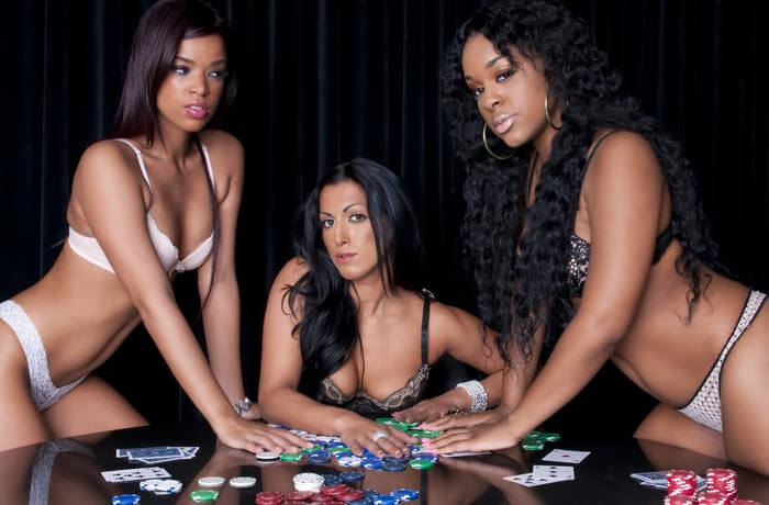 3 gorgeous women at poker table wearing sexy lingerie with poker cards and chips scattered.