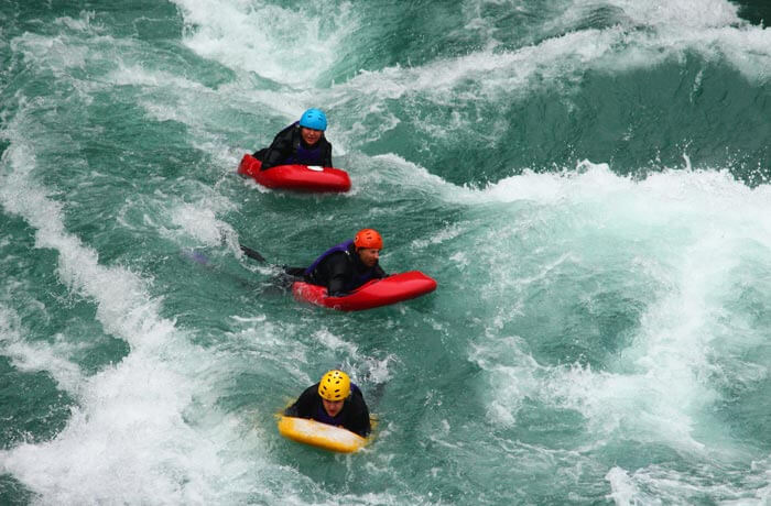 3 People on boards riding rapids with helmets on.