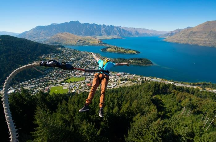 guy in blue shirt jumping backwards with Queenstown scenery in background.